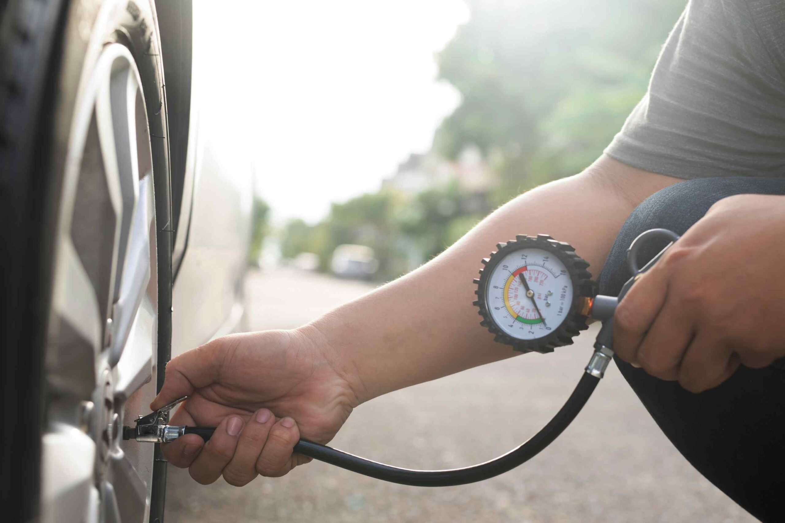 man inflating tire checking air pressure with tire gauge
